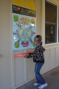 """3rd grader Jenna Blevins affixes on """"The Road to a Greener Planet,"""" the sticker she earned for biking to school."""