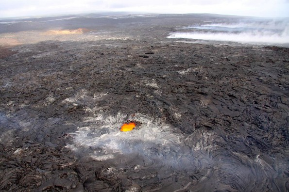 This photograph, looking east, shows a large skylight on the lava tube that is supplying lava to surface flows north of Royal Gardens subdivision. The tube trace, which heads southeast, is marked by the line of fume sources in the upper right portion of the image. The surface flows, out of view in this image, were 1.1 km (0.7 miles) north of the uppermost street in Royal Gardens Thursday (Nov 10). Photo courtesy of USGS/HVO.