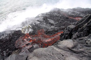 This photograph shows two channels of lava coming over the sea cliff, reaching the new lava delta. Photo courtesy of USGS/HVO