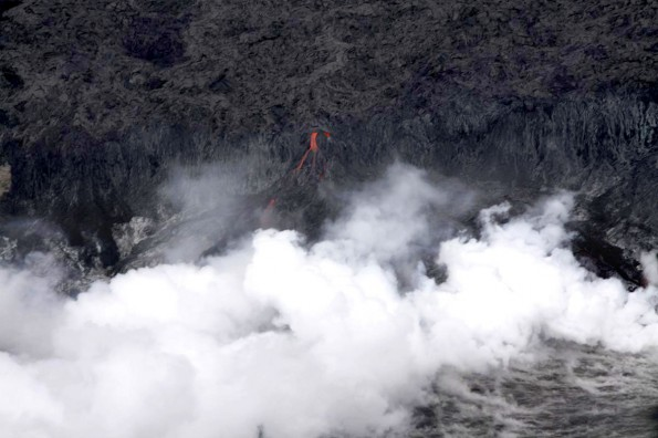 One of the individual streams of lava cascading over the sea cliff, producing a thick steam plume at the water's edge. Photo courtesy of USGS/HVO