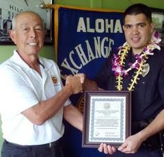 Aloha Exchange Club member Joey Estrella presents an 'Officer of the Month' plaque to Officer Gregory Horton