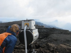 Sulfur dioxide gas emissions from the crater of Pu'u 'O'o on Kīlauea's east rift zone (above) and the vent within Halemaumau Crater at Kilauea's summit create volcanic pollution that affects the air quality of downwind communities. Here, an HVO gas geochemist measures Pu'u 'O'o gas emissions using an instrument that detects gas compositions on the basis of absorbed infrared light. Photo courtesy of USGS/HVO