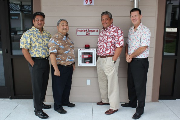 Toby Taniguchi and Barry Taniguchi of KTA Super Stores, Mayor Billy Kenoi, and Bobby Command of the County stand with one of the new AEDs donated by the Taniguchis.
