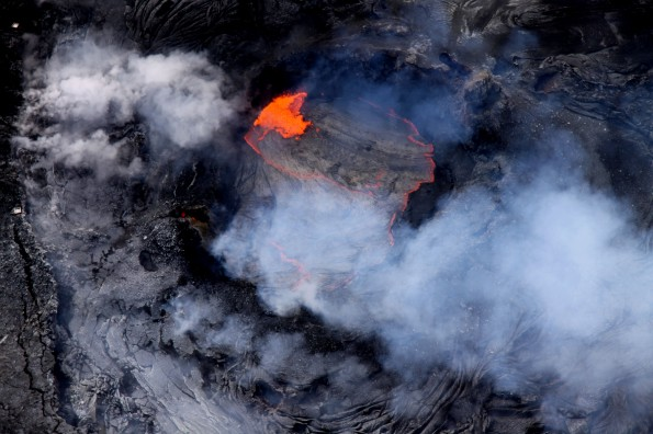 A lava pond has been active in a collapse pit in the eastern portion of Pu'u 'O'o crater for over a month now, with continuous roiling and spattering. For scale, two spatter collection trays - each slightly larger than a lunch tray - can be seen on the crater's rim at the left edge of the image. Photo courtesy of USGS/HVO