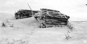 Katmai National Park and Preserve, Alaska. Ash drifts around a house at Katmai after the June 1912 eruption of Novarupta Volcano. August 13, 1912. USGS Photo