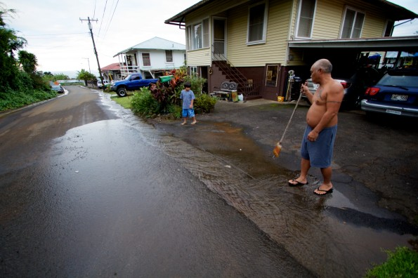 A resident downhill from the damaged pipe sweeps away mud and debris washing down the roadway. Photography by Baron Sekiya | Hawaii 24/7