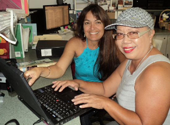 Cindy Naihe reviews computer course with partner family member Aloha Kekauoha. (Photo courtesy of Habitat for Humanity)