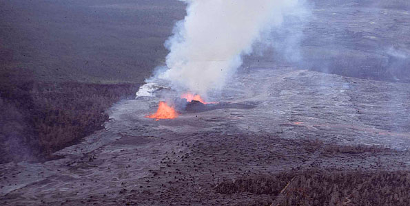 A lava fountain during the opening episode of the Mauna Ulu eruption feeds lava flows that cover Chain of Craters Road.  Both 'Alo'i Crater (lower left) and 'Alae Crater (upper right) were filled with lava later in the eruption. Photo taken on May 28, 1969. Photo courtesy of USGS/HVO