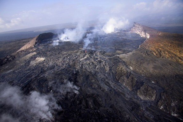 Eruptive activity in Puʻu ʻŌʻō has picked up over the past week. Lava flows erupting sporadically from several places continue to fill the crater and occasionally spill out onto the east flank of Puʻu ʻŌʻō. This view, looking southwest, shows new lava from active and recent flows on Puʻu ʻŌʻō's eastern flank. Many of the flows come directly from the small perched lava lake on the northeast side of the crater floor, visible at the center of the photo. Photo courtesy of USGS/HVO
