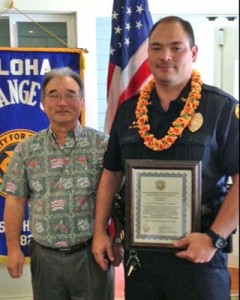 Aloha Exchange Club President Jay Kimura presents an 'Officer of the Month' plaque to Sergeant James Correa.