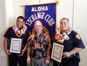 Aloha Exchange Club President Jay Kimura presents an 'Officer of the Month' plaque to Officers Murray Toledo and Luke Watkins