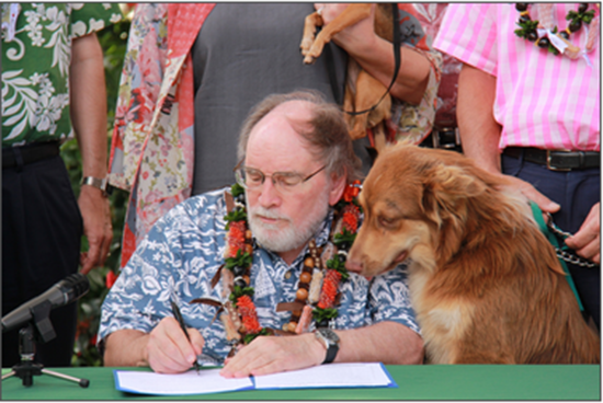 Gov. Neil Abercrombie signs several animal protection bills as Sen. Clayton Hee's dog, Kahekili, and others look on. (Photo courtesy of the Office of the Governor)