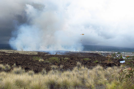 A helicopter makes a water drop on a brush fire near Kohanaiki. (Hawaii 24/7 photo by Andrew Cooper)