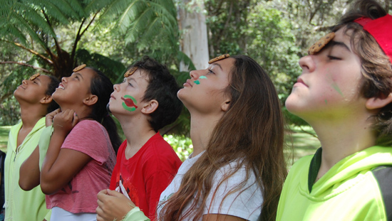 Parker middle schoolers trying to get a cookie from forehead to mouth in a team-building game at their annual campout. (Photo courtesy of Parker School)