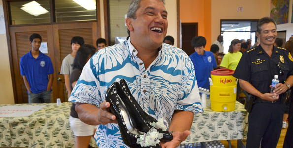 Mayor Billy Kenoi selects a pair of heels for the 2012 Walk-a-Mile event. (Photo courtesy of YWCA Hawaii Island)