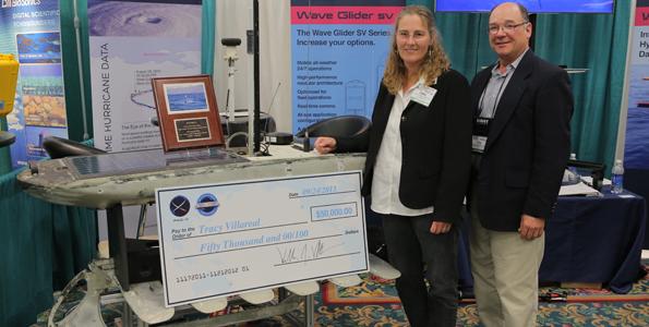 Dr. Villareal and Dr. Cara Wilson pose in front of Wave Glider Benjamin. (Photo courtesy of Liquid Robotics)