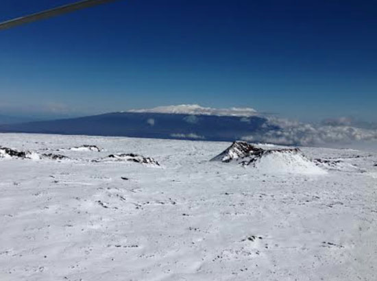 Snow-covered Mauna Loa with the cindercone Pohaku o Hanalei in foreground, near where Sverdlov was spotted. Snow-covered Mauna Kea is seen in the distance. (Photo courtesy of David Okita | Search-and-rescue pilot)