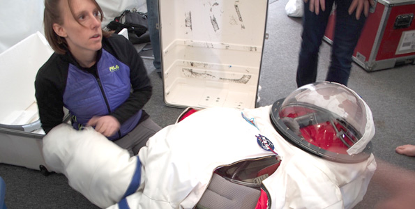 The HI-SEAS training included preparations for donning a simulated space suit, for use during excursions from the habitat. Here, crew member Tiffany Swarmer makes some adjustments with the suit. (Photo courtesy of Ross Lockwood)