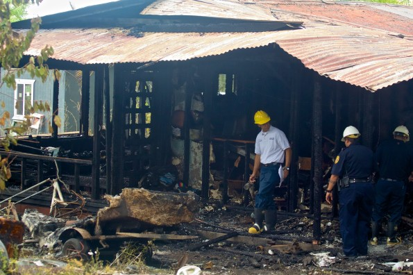 A fire inspector along with police investigate the scene of a fire which destroyed a Kaumana home Friday (June 27). Photography by Baron Sekiya | Hawaii 24/7