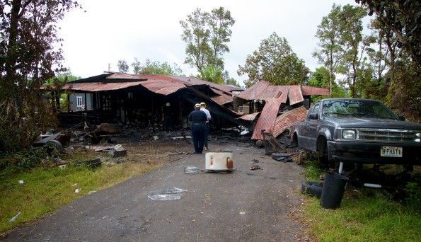 Police and Fire Department personnel investigate the cause of the fire which burned a Kaumana home Friday (June 27). Photography by Baron Sekiya | Hawaii 24/7