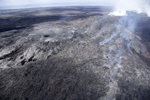 Here is steeper view of the inactive lava pond, just left of center. After it was abandoned, its surface crusted over and sagged to form a gentle bowl. Skylights and points of fume just right of center mark the trace of the new tube. Puʻu ʻŌʻō is at upper right. The view is toward the south-southeast. Photo courtesy of USGS/HVO