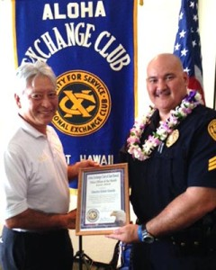 Hilo Exchange Club President Andy Iwashita presents an 'Officer of the Month' award to Detective Robert Almeida.