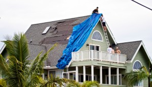 Residents in Hawaiian Paradise Park in Puna work to cover damaged portions of a roof torn away by Tropical Storm Iselle. Photography by Baron Sekiya | Hawaii 24/7