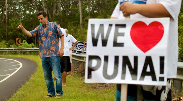 Senator Brian Schatz flashes a shaka sign to passing motorists near Keonepoko Elementary School where two Puna precincts held their delayed primary election polls. Photography by Baron Sekiya | Hawaii 24/7