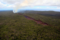 This view looks east at the far end of the June 27th lava flow. In the center of the photograph is an isolated pad of lava which came out of ground crack last week. Further movement of lava within ground cracks has enabled the flow front to advance farther east, with lava issuing from a ground crack in the upper left portion of the photograph, where plumes of smoke mark the location of lava burning forest. Photo courtesy of USGS/HVO