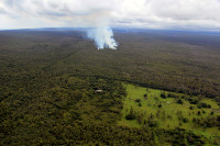 The June 27th lava flow remains active, with lava at the flow front issuing from a ground crack and advancing through thick forest, creating dense plumes of smoke. The farthest lava this afternoon was 13.2 km (8.2 miles) from the vent on Puʻu ʻŌʻō, and 1.3 km (0.8 miles) from the eastern boundary of the Wao Kele o Puna forest reserve. This forest reserve boundary is at the western boundary of Kaohe Homesteads subdivision, a portion of which is visible at the bottom of the photograph. Photo taken Wednesday, September 3, 2014 courtesy of USGS/HVO