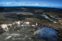 A wide view from the summit, looking east. Halemaʻumaʻu Crater occupies the foreground, with the lava lake in the Overlook crater. At the skyline, Puʻu ʻŌʻō can be seen. The June 27th lava flow is fed from a vent on Puʻu ʻŌʻō, with lava traveling through a lava tube to the flow front. The position of the flow front is marked by a smoke plume as the lava at the front burns vegetation. Photo courtesy of USGS/HVO