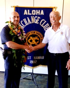 Aloha Exchange board member Joey Estrella presents an 'Officer of the Month' award to Officer Roberto Segobia