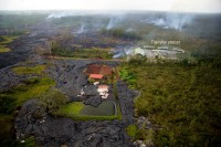 The house which was recently destroyed by lava is just below the center of the photo. Lava bypassed the garage, which still stands at the center of the photo as seen on Wednesday, November 12, 2014. Lava briefly entered the fish pond next to the house, before continuing downslope. Also visible is the small active flow next to the transfer station, and the larger, more rapidly moving finger about 360 meters (390 yards) upslope from Apaʻa Street at upper right. The smoke at upper left marks another breakout widening the flow into the adjacent forest. The view is to the Southwest. Photo courtesy of USGS/HVO
