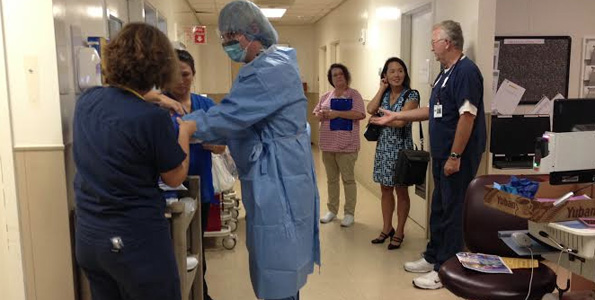 Dr. David Hefer dons personal protective equipment with help of ICU staff/buddies. In background from left to right: Lisa Downing, RN Infection Prevention Director, Dr. Sarah Park, State Epidemiologist, Hawaii DOH and Kevin Brunsen, RN, ICU nurse. (Photo courtesy of Kona Community Hospital)