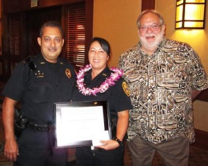 """Lieutenant Juergen Canda and Randy Crowe, president of the Hawaii Island Safety and Security Professionals Association, present a """"Kohala Officer of the Quarter"""" award to Community Policing Officer Kristi Crivello."""