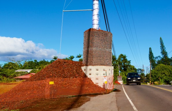 A utility pole hardened against the heat of the lava flow alongside Pahoa Village Road on Sunday, December 7, 2014. Protection material has been pushed off the roadway so it could open to traffic. Photography by Baron Sekiya | Hawaii 24/7