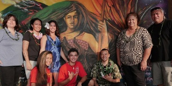 Mele Murals Creative Director Estria Miyashiro (kneeling, right) and students Kayla Cagampang and Kawika Lawrence showcase a mural depicting the battle of Kuamo'o. Standing are: KS West HI Support Services Manager Deeann Haberly, Mele Murals Project Coordinator Mahea Akau, KS Curriculum and Assessment Coordinator Kanakolu Noa, cultural advisor Kalani Hamm and KS Cultural Resource Specialist Mahealani Pai. (Photo courtesy of Mele Murals)