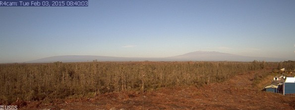 A photo looking west from a research camera temporarily positioned southeast of the Pāhoa Marketplace, this image shows the June 27th lava flow advancing from left to right. Activity is very low so you can see Mauna Loa and Mauna Kea in the distance. The image was taken at 8:40 a.m. Tuesday, February 3, 2015. This camera that took this was installed through a collaboration between the USGS Hawaiian Volcano Observatory, Oceanic Time Warner Cable, and Bryson's Cinders Inc.