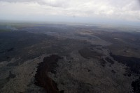 The March 9, 2015 breakouts, which issued from the vicinity of Puʻu Kahaualeʻa, has advanced northward (to the left) and reached the forest at the north edge of the Kahaualeʻa flows and was burning vegetation along its edges. The most recent active pāhoehoe lobes from the February 21st breakout are visible in the foreground. Photo taken Tuesday, March 17, 2015 courtesy of USGS/HVO