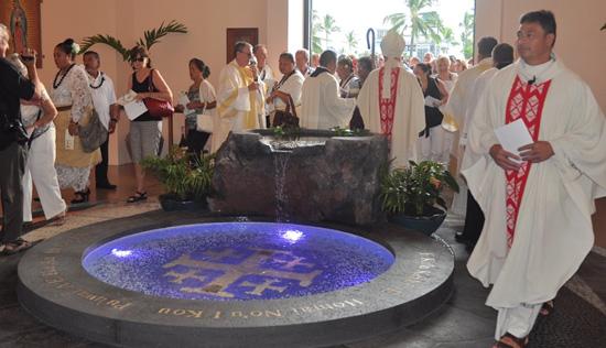 "Father Konelio ""Lio"" Faletoi (right) walks around the new baptismal font. (Photo courtesy of St. Michael the Archangel Church)"