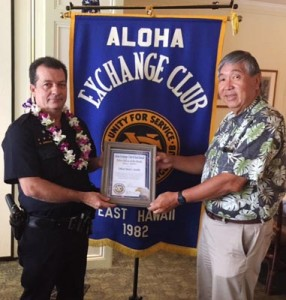 Aloha Exchange board member Curtis Chong presents an 'Officer of the Month' award to Officer Mark Arnold.