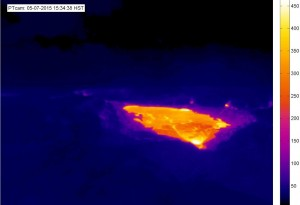 This thermal image of the Puʻu ʻŌʻō crater, sent by text on May 7, 2015, to USGS Hawaiian Volcano Observatory geologists, is an example of the thermal camera alarm system developed at HVO.  In this case, the alarm was triggered by the appearance of new lava on the floor of Puʻu ʻŌʻō, seen here as the brightly colored (hot) region in the image. The temperature scale at right is in degrees Celsius.  USGS webcam image.