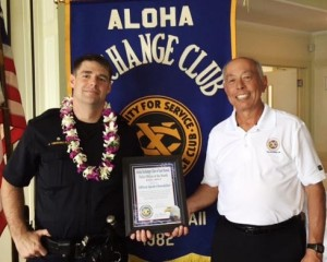 Aloha Exchange board member Joey Estrella presents an 'Officer of the Month' award to Officer Jacob Obermiller.