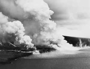 Two of three lava flows that raced down the southwest slope of Mauna Loa on June 2, 1950, are shown here. As lava entered the ocean, steaming water marked its offshore course. A semicircular area of hot, turbulent water killed many fish that were seen drifting on currents or washing up on shore over the next few days. Photo courtesy of U.S. Air Force.