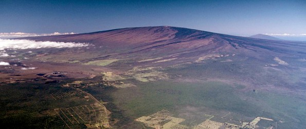 USGS Hawaiian Volcano Observatory scientists are closely monitoring recent signs of unrest on Mauna Loa, the largest active volcano on Earth. In this 1985 aerial photo, Mauna Loa looms above Kīlauea Volcano's summit caldera (left center) and nearly obscures Hualālai in the far distance (upper right). USGS photo.