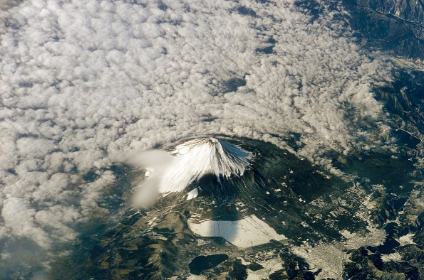 Mount Fuji on the island of Honshu, Japan. The snow-capped inactive volcano, surrounded at lower levels by clouds in this image, lies several miles south of Tokyo. January 26, 2003 Photo via the ill fated Space Shuttle Columbia mission by NASA.