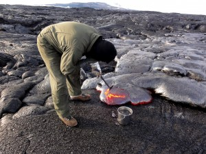 An HVO geologist collects a molten lava sample for chemical analysis, scooping up a bit with the rock hammer to then drop in the water bucket to quench it. Puʻu ʻŌʻō is visible in the distance. Photo taken Wednesday, December 30, 2015 courtesy of USGS/HVO