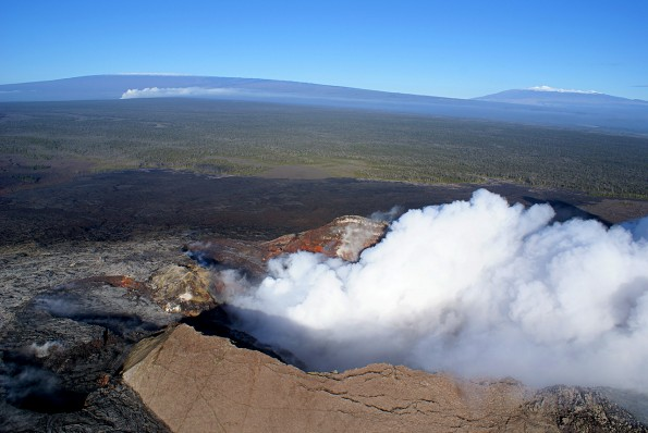 During a kona wind, fume from Pu'u 'Ō'ō (foreground) and Halema'uma'u  Crater (background), both on Kīlauea, blows northward, with towering Mauna Loa and Mauna Kea on the horizon. USGS photo.