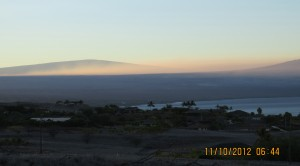 The summit of Mauna Loa (left) rises above the vog layer on the leeward side of the Island of Hawai'i in November 2012. The flank of Hualālai is visible at right. USGS photo.