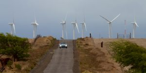A car makes its way down South Point Road with a backdrop of the Pakini Nui Wind Farm. Hawaii 24/7 File Photo